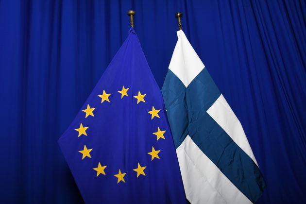 EU:n ja Suomen lippu vierekkäin. Taustalla yksivärinen kangas.