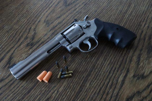 Puupintaiselle pöydälle on asetettu revolveri, patruunoita ja korvatulpat.